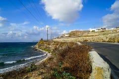 Le bord de la mer a pavé la route le long de l'océan bleu à la plage de baie de Korfos avec l'activité surfante de sports aquatiq Images stock