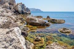 Le bord de la mer rocheux avec de l'eau bleu transparent le plus pur Image libre de droits