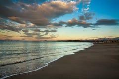Le bord de la mer sur le fond des montagnes et du ciel d'aube opacifie Photographie stock