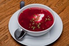 Le borsch ukrainien rouge avec la crème sure dans un plat est sur la table images libres de droits