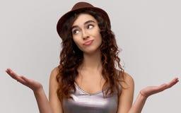Le borse titubanti della giovane donna abbassano il labbro, spande le palme con l'espressione senza tracce, essendo ignare, non p fotografia stock libera da diritti