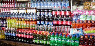 Le bottiglie delle bibite su un mercato accantona Immagini Stock