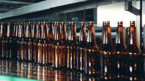 Le bottiglie di vetro stanno muovendo velocemente lungo il trasportatore stock footage