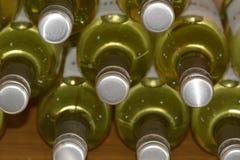 Le bottiglie di vino bianco hanno impilato il livello nel negozio di vino Immagine Stock