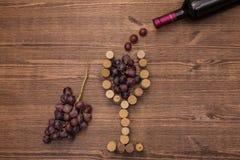 Le bottiglie di vino, di bicchieri di vino, dell'uva e del sughero wine Immagini Stock