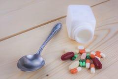 Le bottiglie e le medicine della medicina mettono su un floo di legno fotografie stock