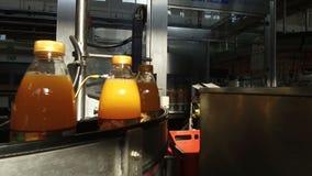 Le bottiglie riempite di succo stanno muovendo lungo il trasportatore video d archivio