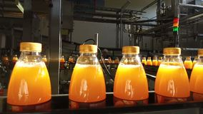 Le bottiglie riempite di succo stanno muovendo lungo il trasportatore stock footage
