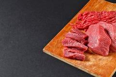 Le boucher frais a coupé l'assortiment de viande sur le fond noir Photographie stock libre de droits