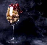 Le bouchon de vin de raisins en verre de vin, érable part dans la fumée photos stock