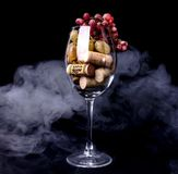 Le bouchon de vin de raisins en verre de vin, érable part dans la fumée image libre de droits