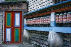 Le bouddhiste coloré de prière roule au fond de porte Photos stock