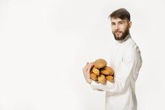 Le boulanger beau dans l'uniforme tenant des baguettes avec du pain enterre o Images stock