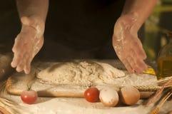 le boulanger d'hommes remet le beurre de malaxage de pâtes de farine de recette, pâte de préparation de tomate et pain de fabrica images stock