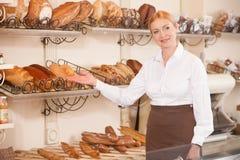 Le boulanger féminin gai invite à sa boutique Photographie stock