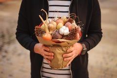 Le bouquet comestible peu commun original de légume et de fruit dans des mains de l'homme Image libre de droits