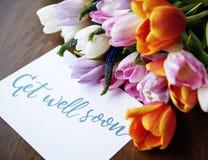 Le bouquet de fleurs de tulipes avec deviennent bon bientôt souhaitant la carte Image stock