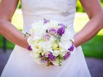 Le bouquet de jeune mariée dans les mains de la jeune mariée photographie stock