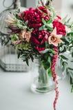 Le bouquet de jeune mariée du mariage fleurit les pivoines rouges et beiges, le lis, verdure dans le vase sur le fond blanc vin d Photo libre de droits