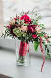 Le bouquet de jeune mariée du mariage fleurit les pivoines rouges et beiges, le lis, verdure dans le vase sur le fond blanc vin d Images stock