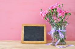 Le bouquet de l'oeillet fleurit dans le vase à côté du tableau noir vide pour l'espace de copie Photos stock