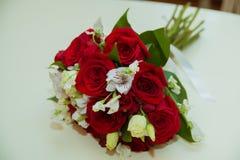 Le bouquet de la belle jeune mariée des roses rouges et des fleurs blanches le jour du mariage image libre de droits