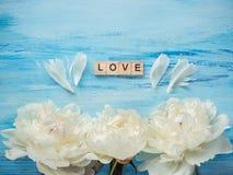 Le bouquet de la floraison, les pivoines blanches et le mot AIMENT Images libres de droits