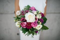 le bouquet de mariage avec grand s'est levé dans la main d'une jeune mariée Photos stock