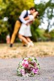 Le bouquet de mariage devant des nouveaux mariés couplent le fond, embrassant le bokeh de profondeur images stock