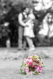 Le bouquet de mariage devant des nouveaux mariés couplent le fond, embrassant le bokeh de profondeur photos stock
