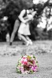 Le bouquet de mariage devant des nouveaux mariés couplent le fond, embrassant le bokeh de profondeur image libre de droits