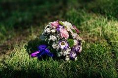 Le bouquet de mariage de l'alstroemeria et des roses se trouve sur l'herbe à la lumière du soleil Images libres de droits