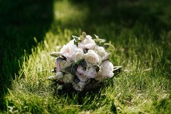 Le bouquet de mariage de la crème et des roses blanches se trouve sur l'herbe à la lumière du soleil Photographie stock