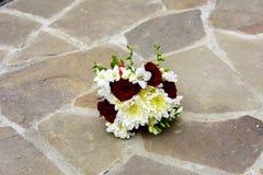 Le bouquet de mariage de la jeune mariée se trouve sur le plancher en pierre Photos stock