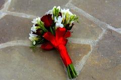 Le bouquet de mariage de la jeune mariée se trouve sur le plancher en pierre Images stock