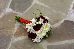 Le bouquet de mariage de la jeune mariée se trouve sur le plancher en pierre Photographie stock libre de droits