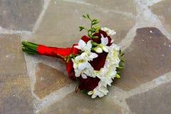 Le bouquet de mariage de la jeune mariée se trouve sur le plancher en pierre Image stock