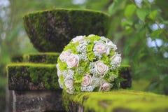 Le bouquet de mariage sur la mousse a couvert la barrière concrète Photographie stock