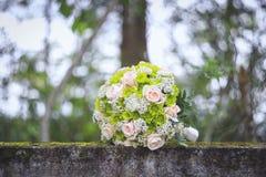 Le bouquet de mariage sur la mousse a couvert la barrière concrète images stock