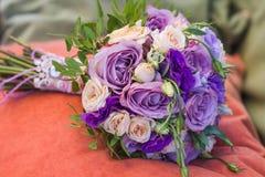 Le bouquet de mariage sur un oreiller orange, bouquet de jeune mariée de s'est levé Photographie stock libre de droits