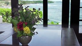 Le bouquet des coûts de fleurs à une fenêtre de maison sur le bord de la mer banque de vidéos