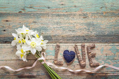 Le bouquet des jonquilles fleurit avec amour d'inscription sur le CCB en bois Photographie stock
