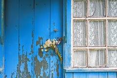 Le bouquet des marguerites a collé dans la poignée de la porte fermée de la vieille maison en bois Images libres de droits