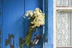 Le bouquet des marguerites a collé dans la poignée de la porte fermée de la vieille maison en bois Images stock