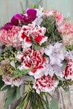 Le bouquet des oeillets rouges et de l'orchidée pourpre fleurit Image libre de droits