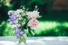 Le bouquet des pivoines, des camomilles et de l'iris blancs fleurit dans le vase en verre Fond d'été Photo teintée Photos stock