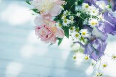 Le bouquet des pivoines, des camomilles et de l'iris blancs fleurit dans le vase en verre Fond d'été Photo teintée Photo libre de droits