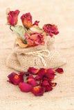 Le bouquet des roses défraîchies sèches et les pétales au-dessus de la jute mettent en sac Photos stock