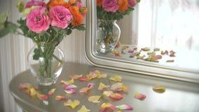 Le bouquet des roses multicolores dans un vase en verre à rond transparent est sur la table avec un miroir 4k, mouvement lent clips vidéos