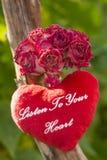 Le bouquet des roses sèches et le coeur de corail de peluche avec le texte écoutent votre coeur Photos libres de droits